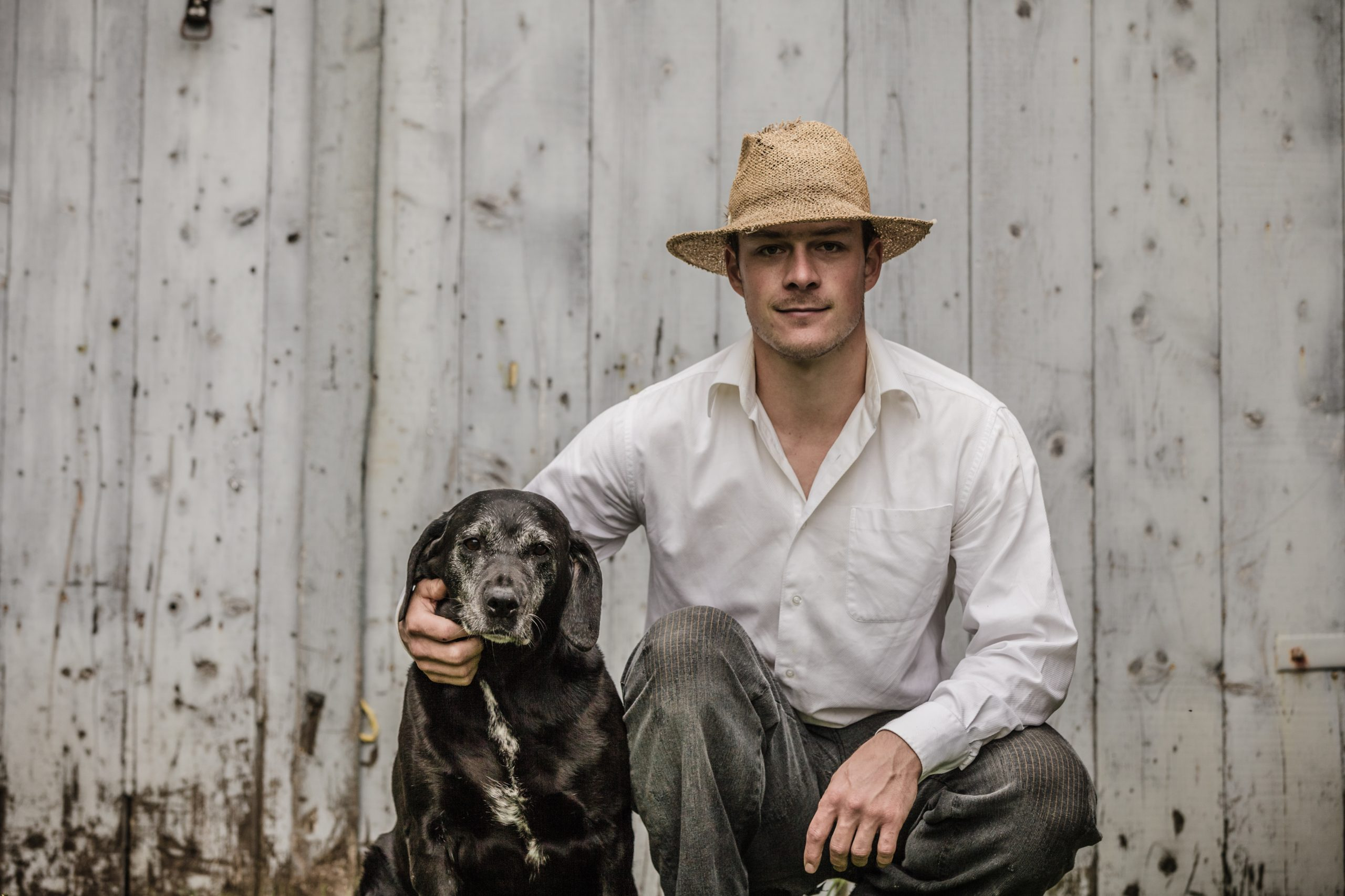 Image of a man wearing a cowboy hat beside a dog